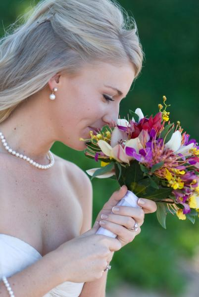 There's nothing more beautiful than a glowing bride on her wedding day. Here you see a photo of a bride enjoying the aroma of her unique wedding bouquet.